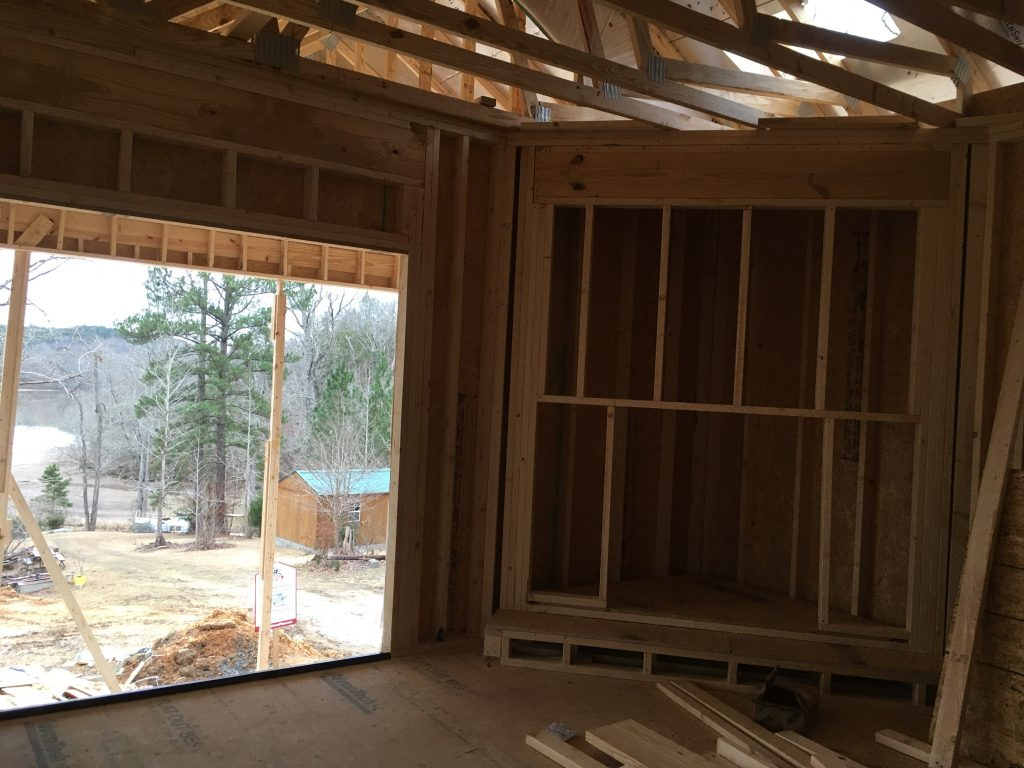 The fire place is framed out next to the frame for one of the sliding glass doors.